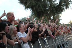 Folla di concerto che incoraggia dietro la barriera immagine stock