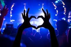 Folla di festival che solleva le mani nella parte anteriore di concerto di musica della st luminosa Fotografia Stock