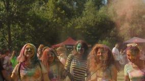 Folla emozionante delle ragazze che spruzzano la polvere di colore per ventilare accogliersi stock footage