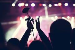 Folla incoraggiante ad un grande concerto rock Mani sulla siluetta con una rosa Immagine Stock