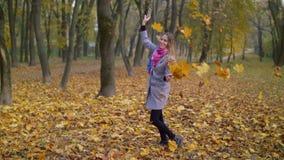 Follaje que lanza sonriente alegre de la mujer en otoño almacen de video