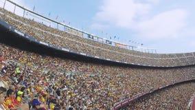 Folle dei fan sulle tribune su stadio di football americano in Spagna Giocatori sul campo Albero nel campo supporto video d archivio
