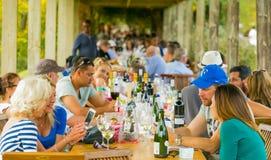Folle della gente che si siede all'area pranzante dell'evento del vino immagine stock