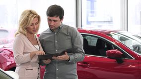 Folleto maduro de la lectura de los pares en la concesión de coche que compra un nuevo auto almacen de video