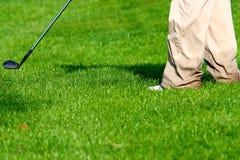 Follow through. A golfer making a chip shot with an iron Royalty Free Stock Photos