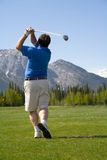 Follow Through. A golfer tees off on Kananaskis Golf Course in the Rocky Mountains royalty free stock images