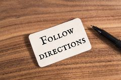 Follow directions word. Write in card on wood background Stock Photography