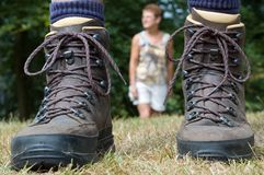 Follow the hiker -1. Woman following the hiker. Hiking boots in front royalty free stock photography