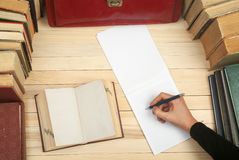 Follow the law. Professional lawyer sitting at the table and signing papers. On a wooden table books, documents, red. Briefcase royalty free stock photo