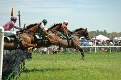 Follow the leader. Horses and riders clear the jump during steeplechase Royalty Free Stock Photography