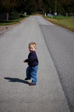Follow Me. One year old boy taking a walk on a long rural road Royalty Free Stock Photos