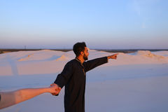 Follow me Arab guy and European woman who walks by hand in deser Stock Photos