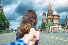 Follow me, Attractive brunette girl holding the hand leads to the red square in Moscow. Russia. royalty free stock photography