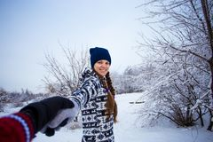Follow me. Attractive young woman in hat holding hand of her boyfriend and walking. In winter park Royalty Free Stock Photo