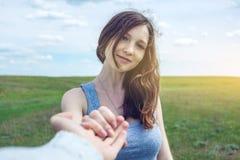 Follow-me, attraktives Brunettemädchen, welches die Hand der Führungen auf einem sauberen grünen Gebiet, Steppe mit Wolken hält stockfotografie