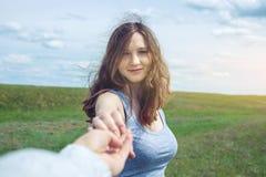 Follow-me, attraktives Brunettemädchen, welches die Hand der Führungen auf einem sauberen grünen Gebiet, Steppe mit Wolken hält lizenzfreies stockfoto