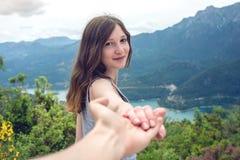 Follow-me, attraktives Brunettemädchenhändchenhalten mit Führungen im Gebirgstal mit Fluss stockbilder