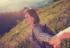 Follow me. Beautiful young laughing woman holds the hand of a man on sunny field stock photos
