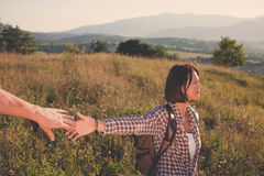 Follow me. Beautiful young laughing woman holds the hand of a man on sunny field Stock Photography