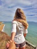 Follow-me Blondes Mädchen, das zurück auf der Randklippe steht Lizenzfreies Stockfoto