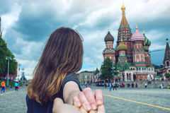Follow me, brunette girl holding the hand leads to the red square in Moscow. Russia. stock photos