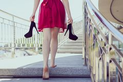 Follow me classic chic classy clothing after dancing prom concept. Gorgeous cute happy teen student holding black stilettos pumps. In hands standing ground royalty free stock photo