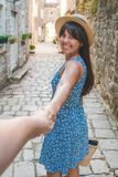 Follow me concept. woman pull man by hand at small streets of perast royalty free stock photo