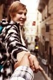 Follow me Concept Woman pulling Man Hand toward street Stock Photo
