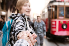 Follow me Concept Woman pulling Man Hand toward Train Stock Photo