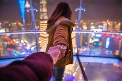 Follow me couple traveling in oriental pearl TV tower. Woman red hair in orange jacket holding man by hand going to night view of city in shanghai. Traveling royalty free stock images