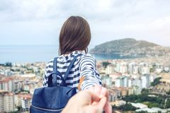 Follow-me, das attraktive Brunettemädchen, welches die Hand hält, führt in die Küstenstadt von einer Höhe lizenzfreies stockfoto