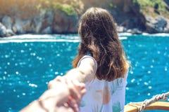 Follow-me, das attraktive Brunettemädchen, welches die Hand hält, führt zu die Berge und das blaue Meer stockfotos