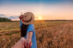 Follow me in the field. Traveling together. Follow me. Young woman in straw hat holding boyfriend`s hand walking in the field on sunset royalty free stock image
