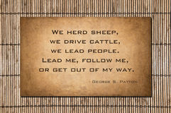 Follow me - George S. Patton. We herd sheep, we drive cattle, we lead people. Lead me, follow me, or get out of my way. George S. Patton. Quote over stone and Royalty Free Stock Photography