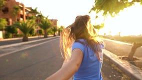 Follow-me - glückliche junge Frau, die hand- an einem hellen sonnigen Tag Hand in Hand laufen des Kerls zieht stock video footage