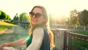 Follow-me - glückliche junge Frau, die Kerl ` s hand- an einem hellen sonnigen Tag Hand in Hand gehen zieht stock video