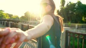 Follow-me - glückliche junge Frau, die Kerl ` s hand- an einem hellen sonnigen Tag Hand in Hand gehen zieht stock video footage