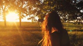 Follow-me - glückliche junge Frau, die Kerl ` s hand- an einem hellen sonnigen Tag mit einem Smartphone Hand in Hand gehen und zi stock video