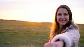 Follow-me - glückliche junge Frau gibt einem Kerl Hand - Hand in Hand, gehend an einem hellen sonnigen Tag stock footage