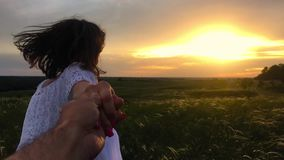 Follow me. Happy couple taking hands and having fun outdoors. Couple running away on the meadow. Countryside. Slow stock video footage