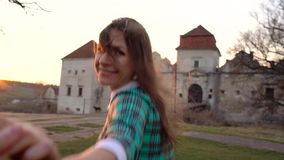 Follow me - happy young woman pulling guy`s hand against the background of an old castle stock video
