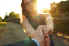 Follow me - happy young woman pulling guy`s hand - hand in hand Stock Photos