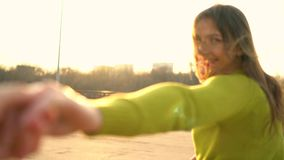 Follow me - happy young woman pulling guy`s hand - hand in hand walking on a bright sunny day stock footage