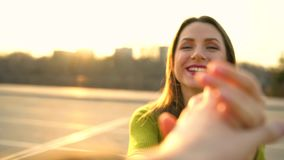 Follow me - happy young woman pulling guy`s hand and sends an air kiss - hand in hand walking on a bright sunny day stock video