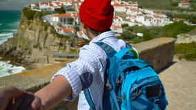 Follow me - happy young woman in a red hat and with a backpack behind her back pulling guy`s hand at Azenhas do Mar stock footage