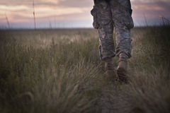 Follow me. Person in camouflage walking towards a horizon Stock Images