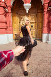 Follow me the photo. Blonde girl holding the hand and goes to. The big door. concept of travel Royalty Free Stock Image
