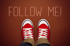 Follow Me Request Concept. For Social Networking on Internet with Young Person in Red Sneakers from Above Royalty Free Stock Images