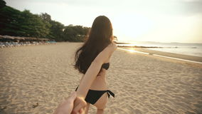 Follow me shot of young girl in a bikini running and holding man hand on the beach in sunset stock footage