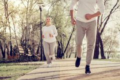 Sporty man jogging outdoors with his wife stock images